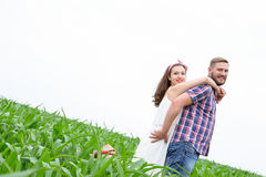 Happy loving young adult couple spending time on the field on sunny day. Happy young adult couple in love spending time on the field on sunny day outdoors royalty free stock image