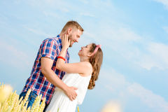Happy loving young adult couple spending time on the field on sunny day. Happy young adult couple in love spending time on the wheat field on sunny day outdoors royalty free stock image
