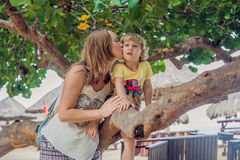 Happy loving young mother kisses her toddler son on the walk Stock Image
