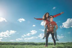 Happy loving young people having fun in nature. I believe we can fly. Full length of amorous couple looking at blue sky. Girl is on her boyfriend back with royalty free stock image