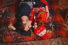 Happy loving young people having fun near the Christmas tree on the floor. Smiling couple celebrating New Year. Toned Royalty Free Stock Photos