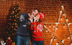 Happy loving young people having fun near the Christmas tree. Smiling couple celebrating New Year. Toned image. Royalty Free Stock Photos