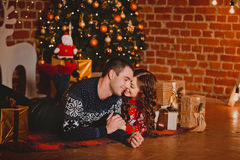 Happy loving young people having fun near the Christmas tree. Smiling couple celebrating New Year. Toned image. Royalty Free Stock Photo