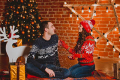Happy loving young people having fun near the Christmas tree. Smiling couple celebrating New Year. Toned image. Stock Photos