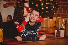 Happy loving young people having fun near the Christmas tree. Smiling couple celebrating New Year. Toned image. Stock Image