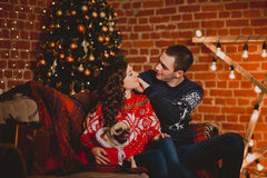 Happy loving young people and pug dog having fun near the Christmas tree. Smiling couple celebrating New Year. Toned Stock Image