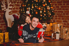 Happy loving young people and pug dog having fun near the Christmas tree. Smiling couple celebrating New Year. Toned Royalty Free Stock Image