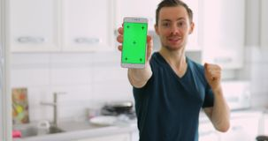 Happy lucky man showing empty green screen of smart phone at home. Happy lucky man showing an empty green screen of smart phone at home stock footage