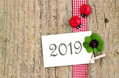 Happy, Lucky New Year 2019. New Years card  for 2019 with leafed clover and ladybugs on wooden background Royalty Free Stock Image