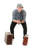 Happy lucky traveller with vintage suitcases. Happy lucky young male traveller with two old vintage suitcases rubs his hands isolated on white background Stock Images