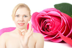 Happy lucky young woman. With ok gesture on background with rose. Concept of sweet life Stock Photo