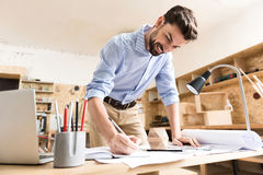 Happy lumber craftsman creating rough copies of product in workshop Royalty Free Stock Images