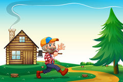 A happy lumberjack carrying an axe while walking near the wooden Stock Photography