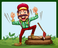 A happy lumberjack stepping on a log with axe Stock Photography