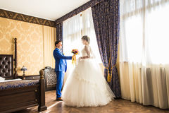 Happy luxury bride and groom standing at window light in rich room.  Royalty Free Stock Images
