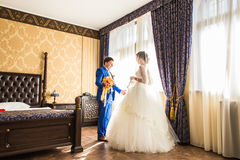 Happy luxury bride and groom standing at window light in rich room.  Royalty Free Stock Photos