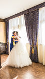 Happy luxury bride and groom standing at window light in rich room.  Royalty Free Stock Image