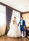Happy luxury bride and groom standing at window light in rich room.  Royalty Free Stock Photography