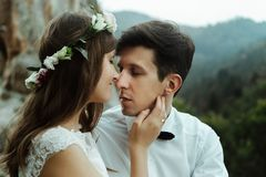 Happy luxury couple of newlyweds hugging with tender on the top. Of a mountains in the evening royalty free stock image