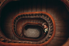 Happy luxury wedding couple is standing and kissing on the stairs Royalty Free Stock Image