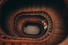 Happy luxury wedding couple is standing and kissing on the stairs Stock Photos