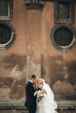 Happy luxury wedding couple is standing and kissing in the streets of old city Royalty Free Stock Images