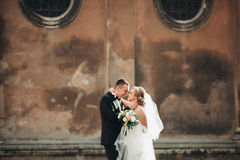 Happy luxury wedding couple is standing and kissing in the streets of old city Stock Photo