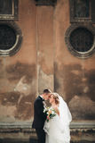 Happy luxury wedding couple is standing and kissing in the streets of old city Royalty Free Stock Photo