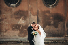Happy luxury wedding couple is standing and kissing in the streets of old city Royalty Free Stock Image