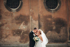 Happy luxury wedding couple is standing and kissing in the streets of old city Stock Images