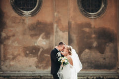 Happy luxury wedding couple is standing and kissing in the streets of old city Royalty Free Stock Photography