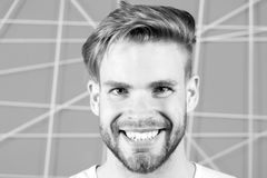 Happy macho with beard on unshaven face. Bearded man smile with blond hair and stylish haircut. Guy with healthy young. Skin face. Hair care in salon or stock images