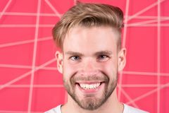 Happy macho with beard on unshaven face. Bearded man smile with blond hair and stylish haircut. Guy with healthy young skin face. Hair care in salon or stock photography