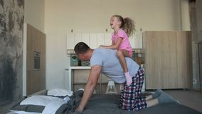 Father giving piggyback ride to daughter at home stock footage