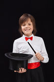Happy magician boy on black background. With magic wand and hat royalty free stock photography