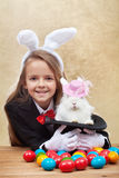 Happy magician girl holding cute bunny in magic hat Stock Images