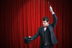 Happy magician or illusionist is showing magic trick with his wand. Red curtains in background.  Stock Photography