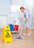 Happy maid cleaning floor with mop Stock Photo