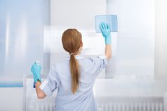 Happy maid cleaning glass Stock Photo