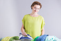Happy maid doing the ironing Stock Photography