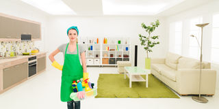 Happy maid after home cleaning. Young caucasian woman standing in clean house holding cleaning products royalty free stock photo