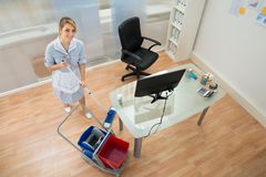 Happy maid with mop in office Stock Photo