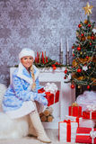 Happy Maiden Girl Holding Christmas Present at Fireplace Royalty Free Stock Photography