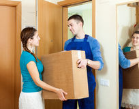 Happy mailman  in uniform brought package to girl at home Royalty Free Stock Photos
