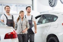 Happy maintenance engineers looking away in automobile repair shop Stock Photo