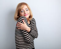 Happy makeup blond woman hugging herself with natural emotion on Stock Image