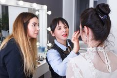 Makeup tutorial lesson at beauty school. Happy makeup teacher with her student girl. Makeup tutorial lesson at beauty school. Make up artist work in her studio royalty free stock photography