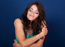 Happy makeup woman hugging herself with natural emotional enjoyi. Ng face. Love concept of yourself body and face on blue background Royalty Free Stock Photo