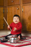 Happy Making Noise. Baby girl delighted with the noise she's making banging on pots and pans with a wooden spoon Stock Photos