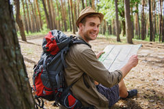 Happy male adventurer navigating in forest Royalty Free Stock Images